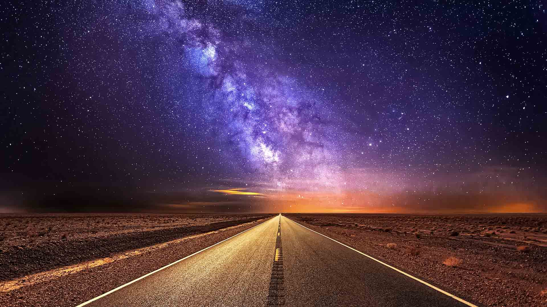 Road in the desert and the purple milky way
